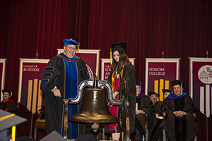 Dr. C.J. Vires, vice president of academics and provost at Freed-Hardeman University, watches as Isabel Harris, winner of the Faculty Scholarship-:Leadership Medal, prepares to toll the bell ending the 2018-19 school year.