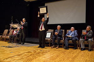 Kyo Jhin hoists the certificate declaring him a Distinguished Alumnus following a presentation in chapel.