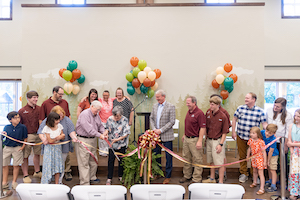 Members of the Tucker family and the Mid-South Youth Camp family come together to cut the ribbon for the Tucker Family Dining Hall.