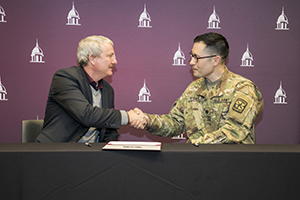 FHU President David Shannon and Lt. Col. Lowell Howard,  ROTC commanding officer at the University of Tennessee at Martin, shake hands after signing an agreement to offer an Army ROTC program on FHU