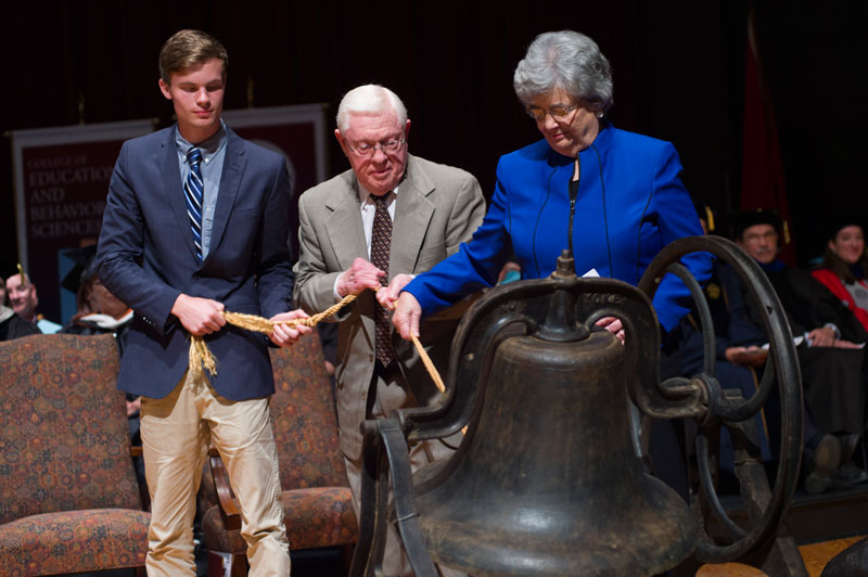 "Clyde Woods, wife Ann and freshman Matthew Johnson serve as ""Masters of the Bell"""